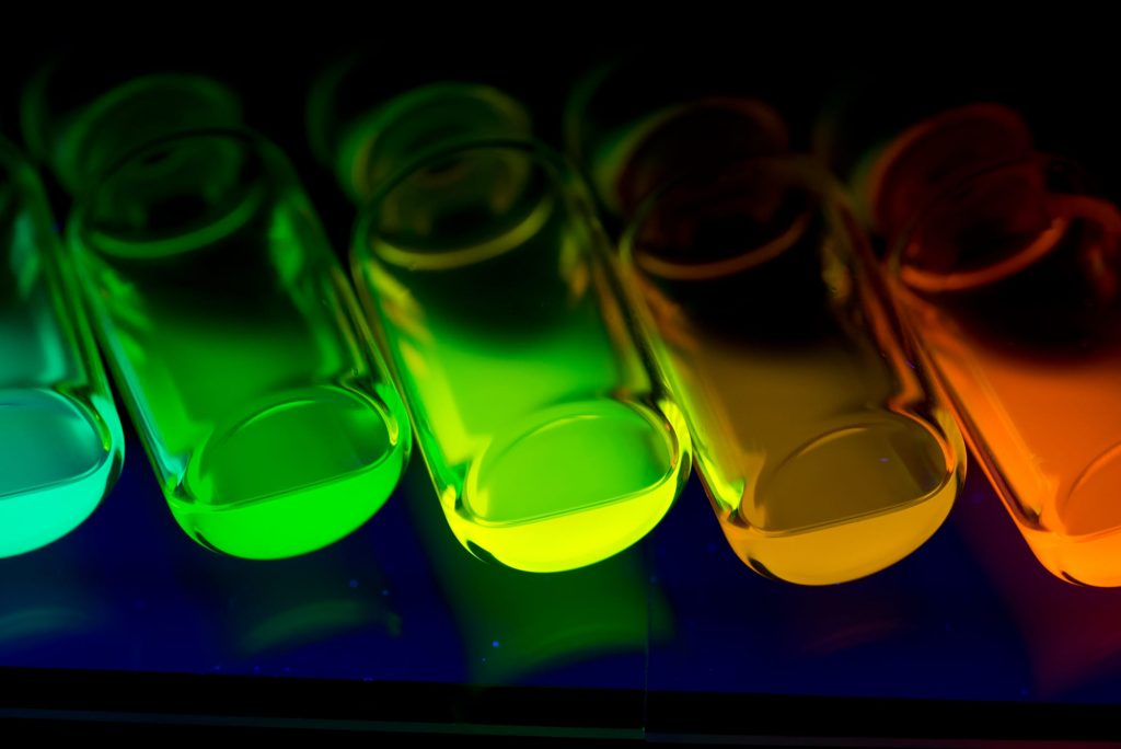 A photograph of fluorescing chemicals produced by a Syrris Asia flow chemistry system