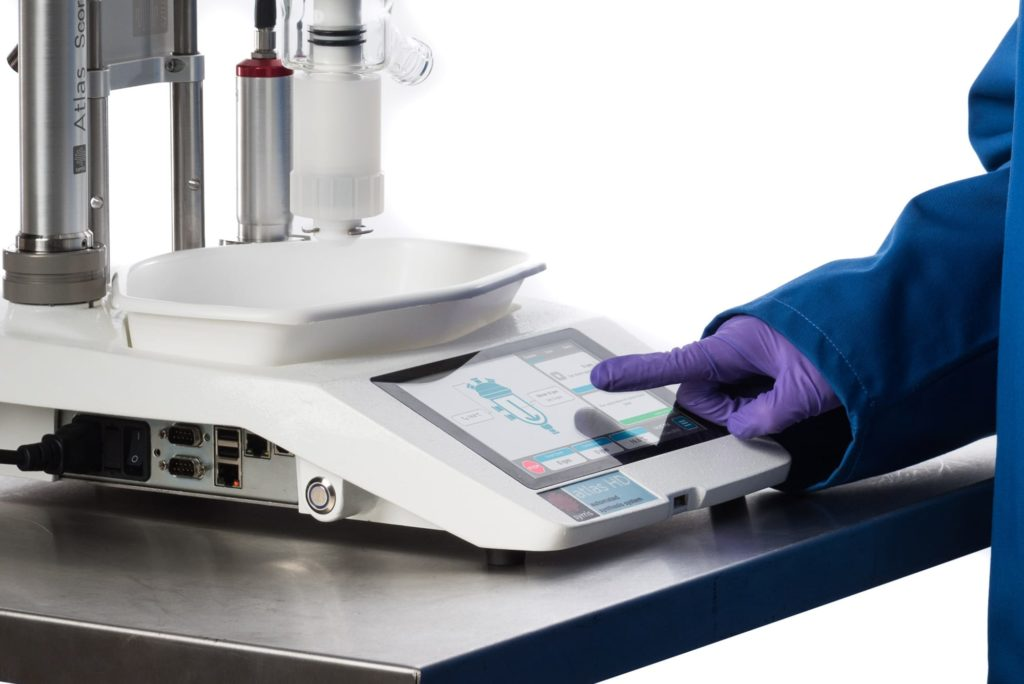 A photograph of a chemist using the Atlas HD touch screen base