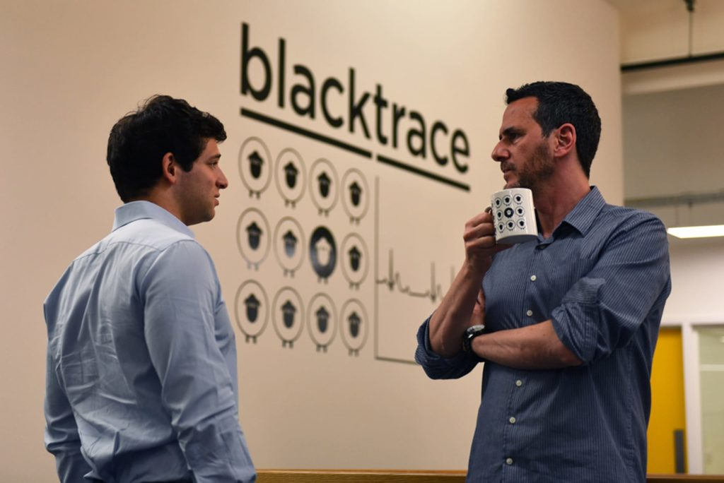 Syrris employees in front of the Syrris/Blacktrace Holdings Ltd logo