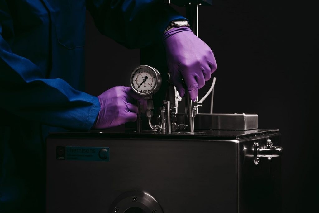 A close up photograph of a chemist removing the reactor from the Chemisens housing unit