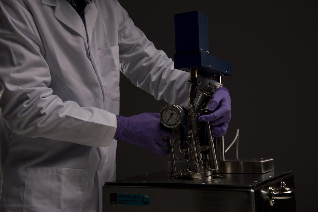 A photograph of a chemists assembling a Syrris Chemisens Calorimeter