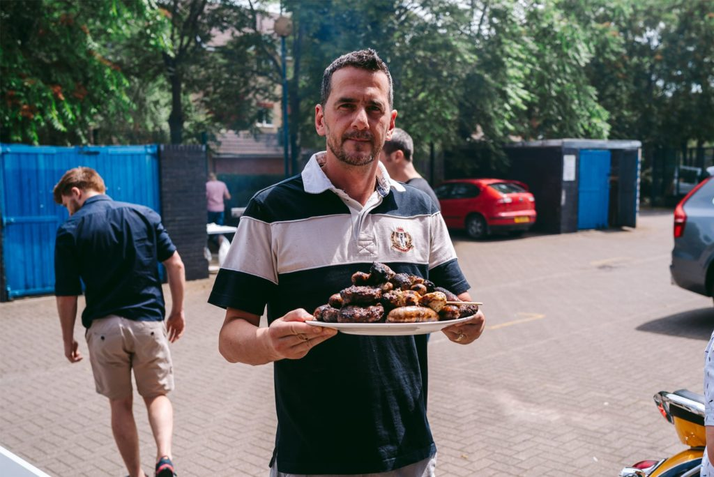 A photograph of Syrris employee, Leandro, with a plate of meat during the Syrris Summer BBQ
