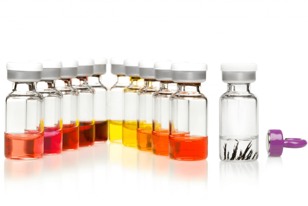 A photograph of several glass vials, filled with nanoparticles produced on Syrris Asia flow chemistry systems