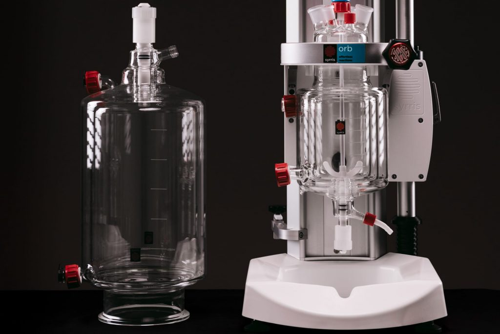 A photograph of an Orb Jacketed Reactor and a spare glass vessel